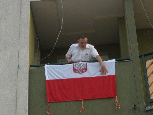 Paweł Porębski wiesza flagę przed świętem Wojska Polskiego