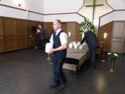 Przenoszenie urn do karawanu pogrzebowego